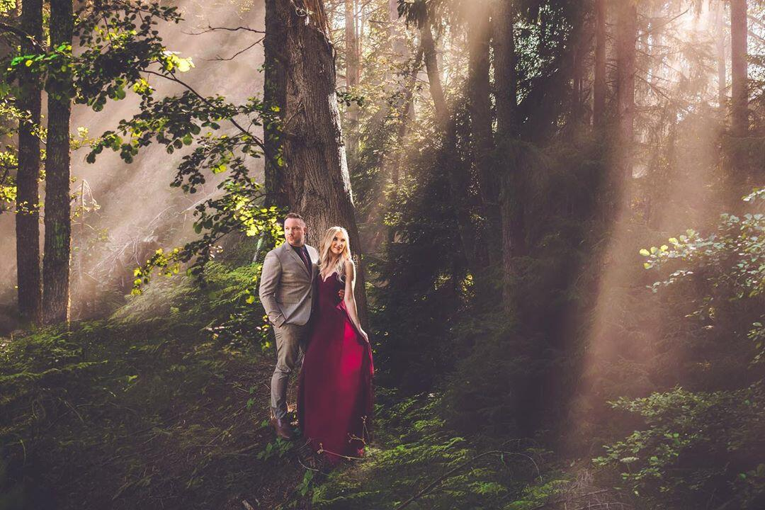 A couple posing for an engagement session in the forest with sun rays coming from the gaps between trees.