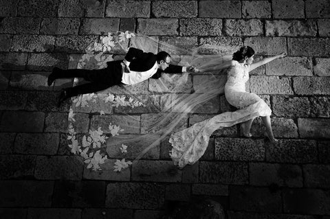 Black and white capture of a bride and groom posing as superheroes while lying on the ground
