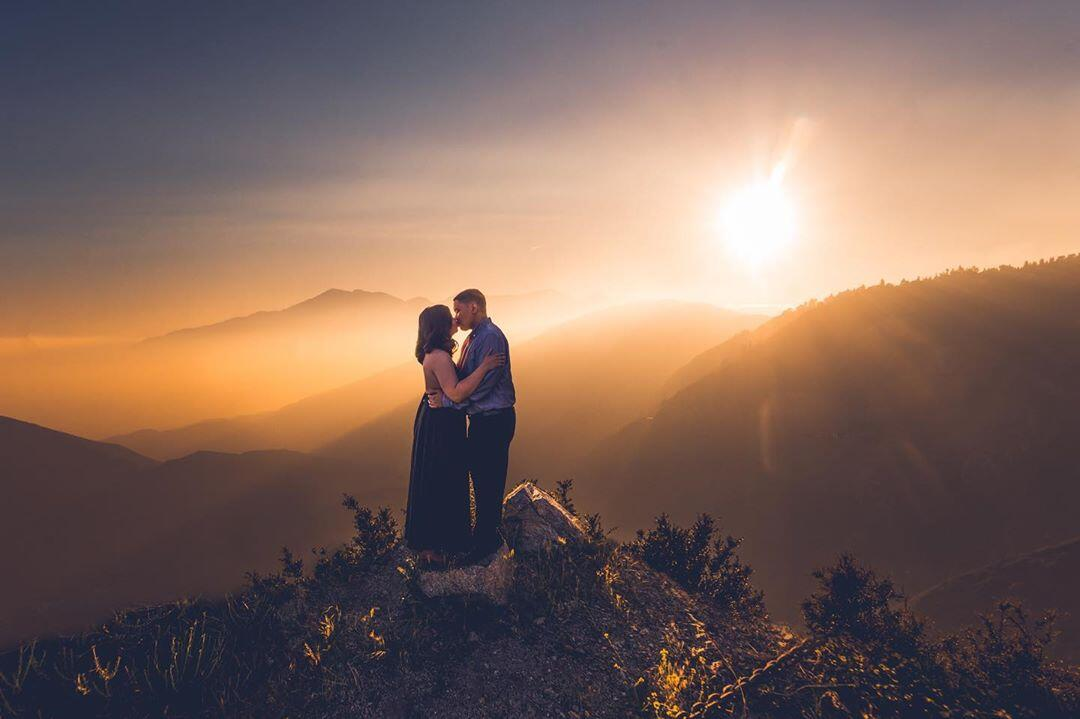 couple kissing on mountain at sunset