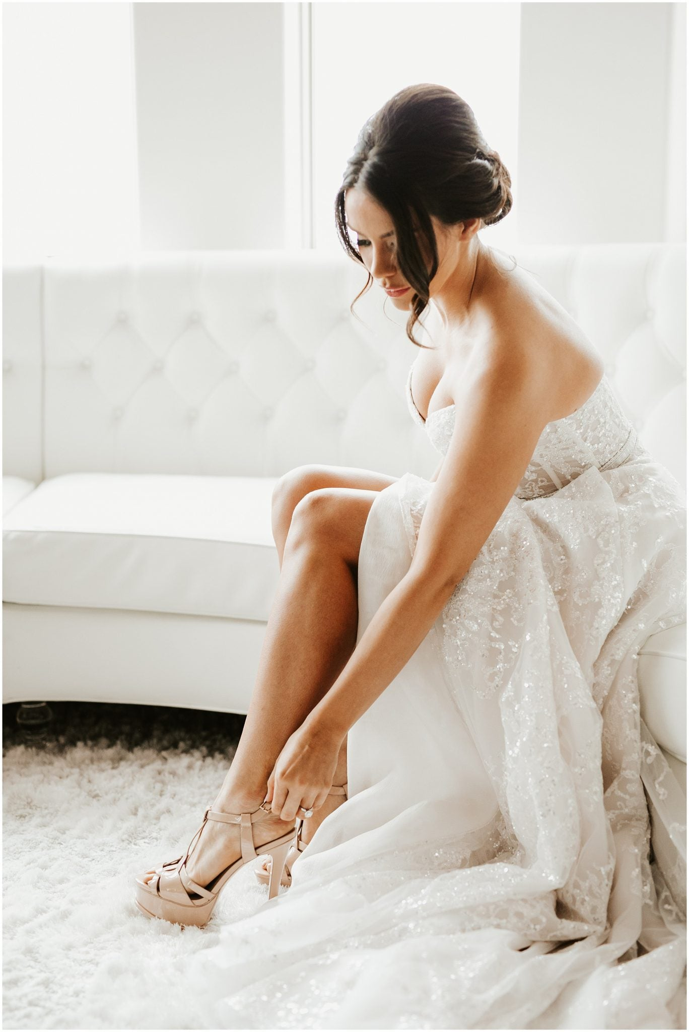 A bride posing for a picture while bending down to buckle her shoe