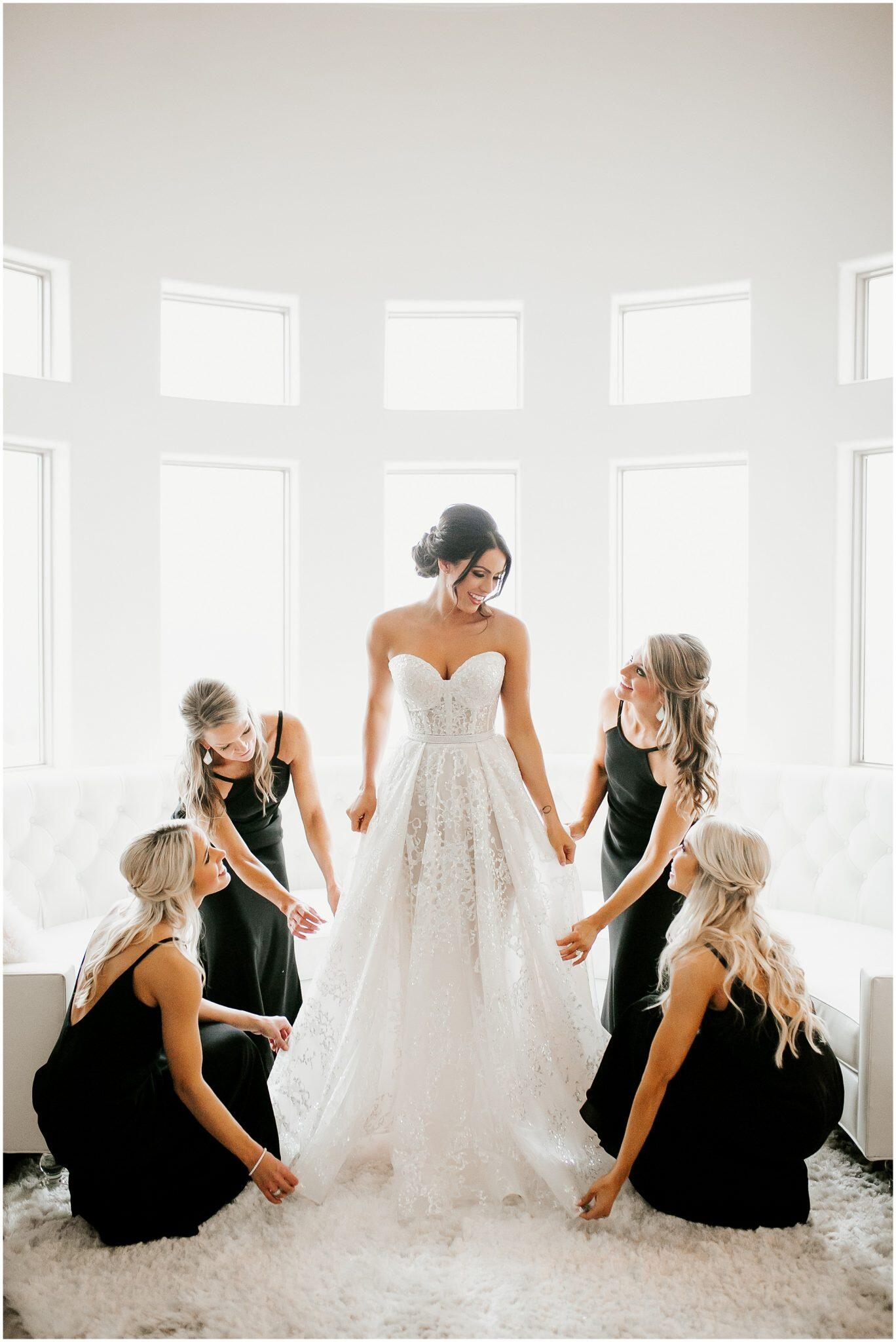 bride standing in getting ready room with bridesmaids all around her