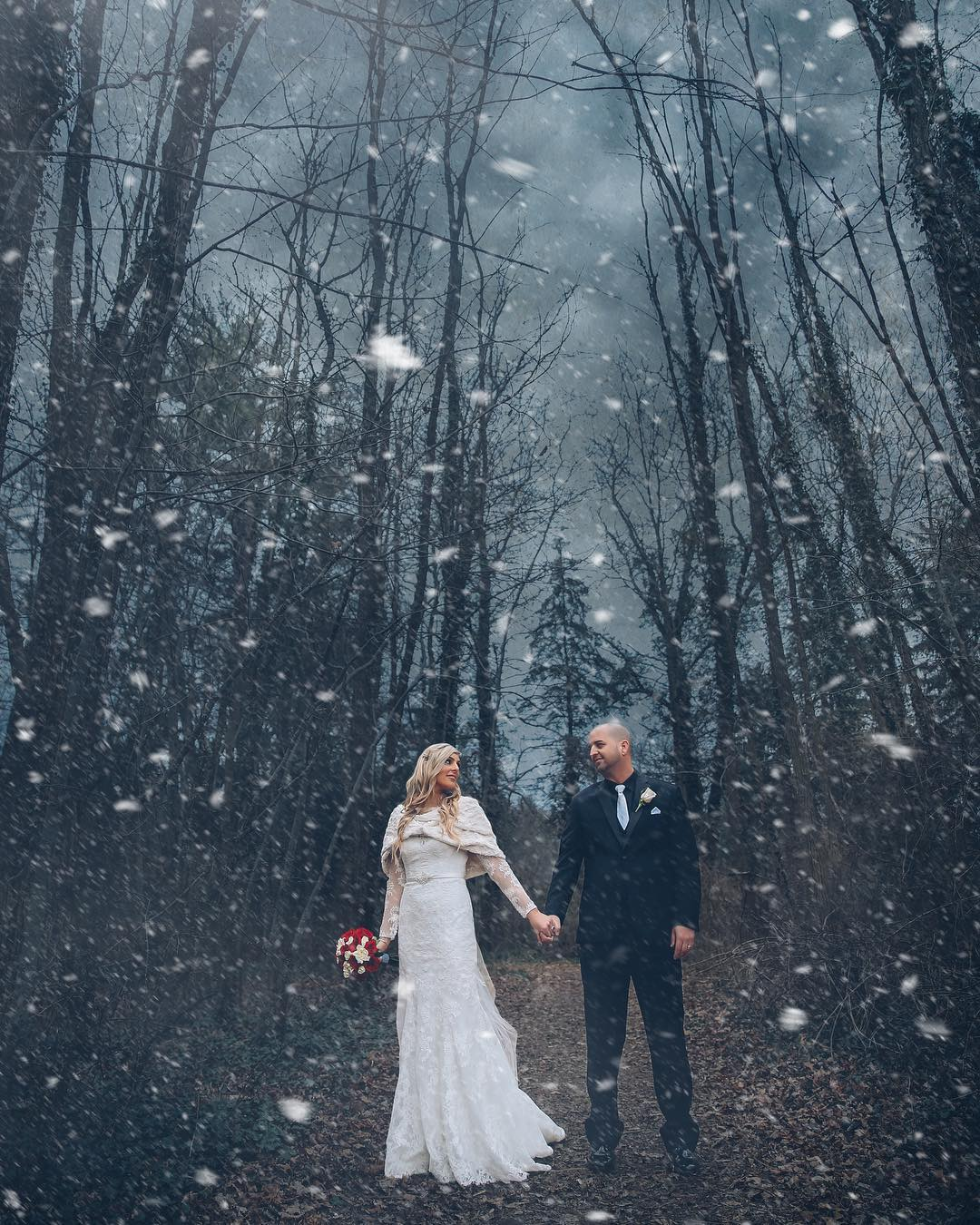 Bride and groom posing while holding hands as the snow falls