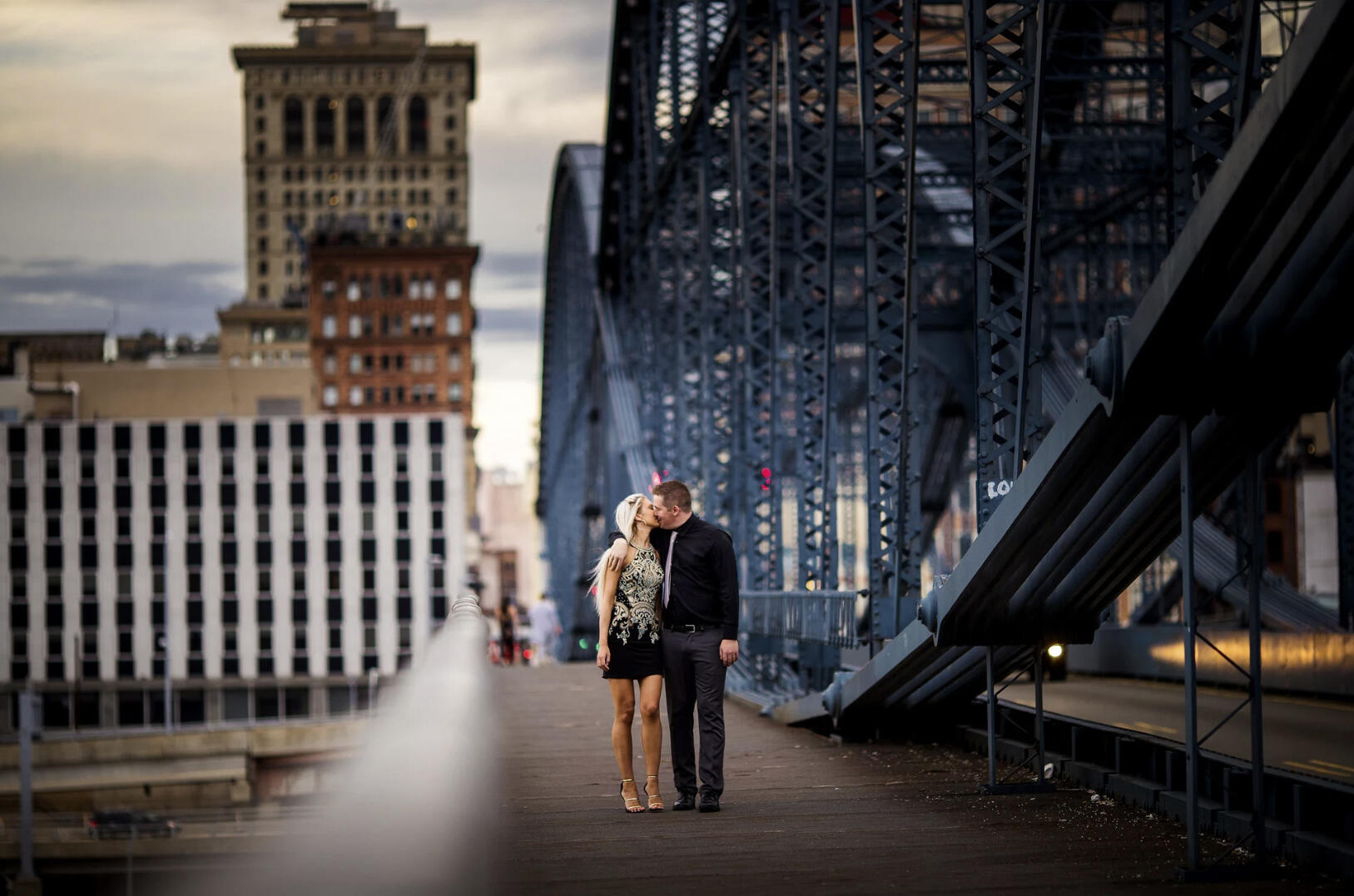 couple kissing by bridge in pittsburgh