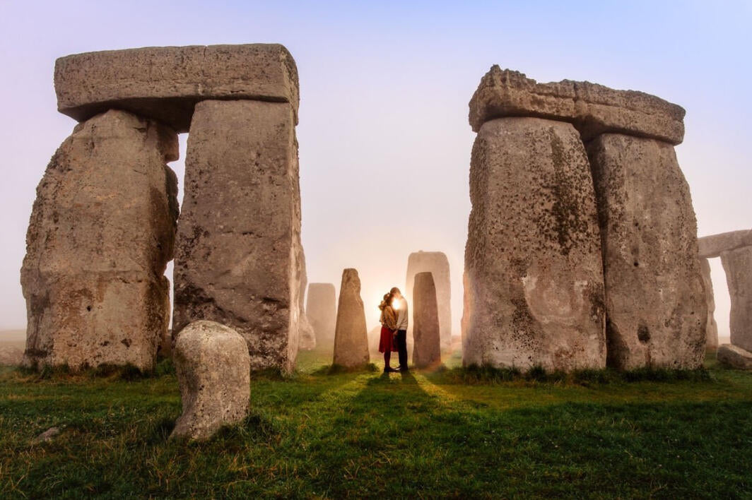 couple standing forehead to forehead at Stonehenge at sunrise