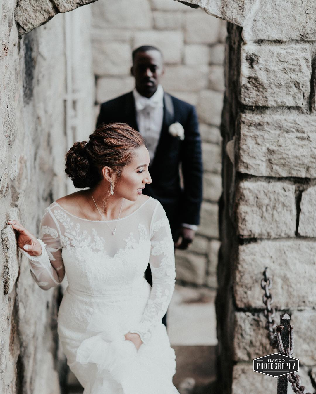 First look photo of a bride standing near a wall with groom standing behind her
