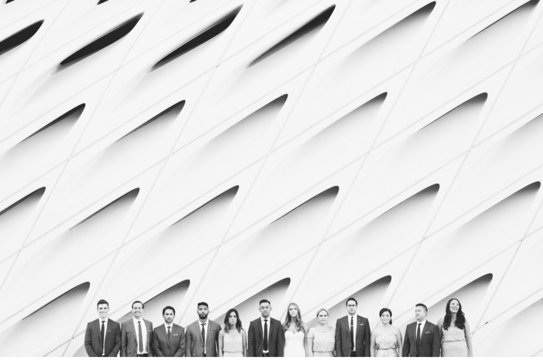 Black and white image of a bride and groom posing with the groomsmen and bridesmaids in front of a uniquely designed wall