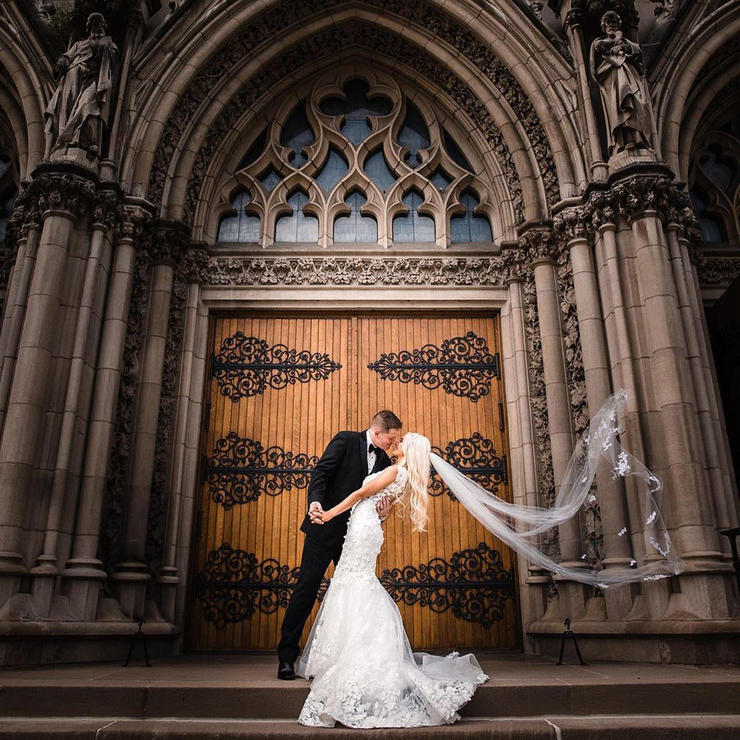 A bride an groom embracing on cathedral steps while the bride's veil flows in the wind.