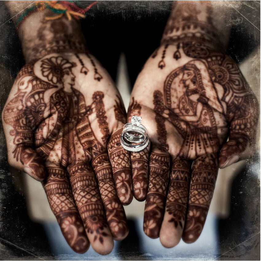 Close up of a bride's heena tattooed hands with the engagement ring