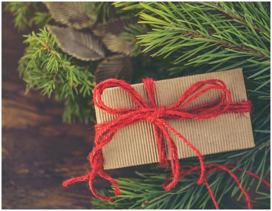 A small present wrapped with brown paper and decorated with a red bow