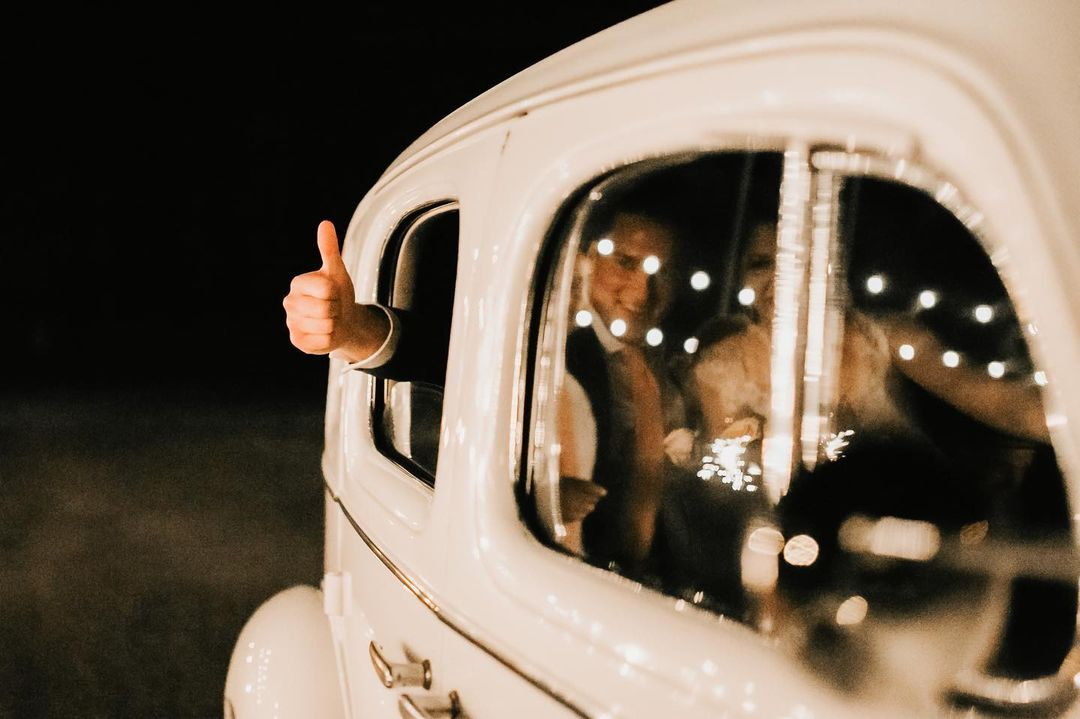 Bride and groom seated inside a white car for making the exit with groom showing a thumbs up from the car's window