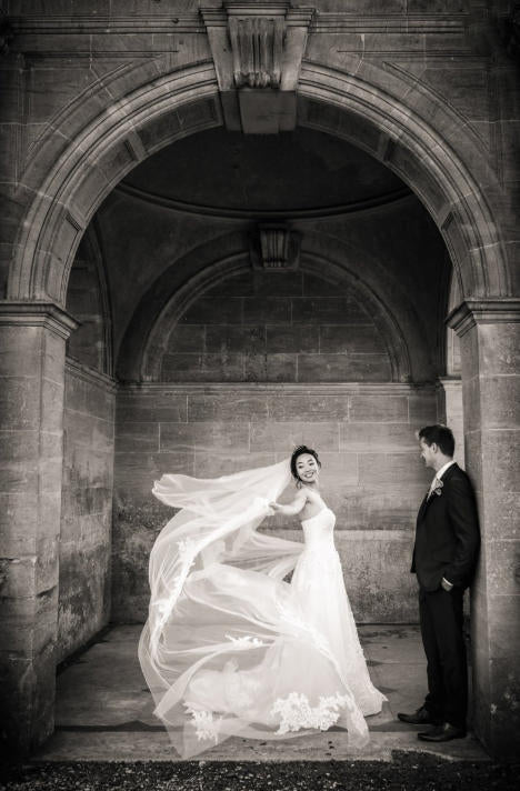 A stunning wedding photography shot of a bride and groom in an archway. by SDE customer