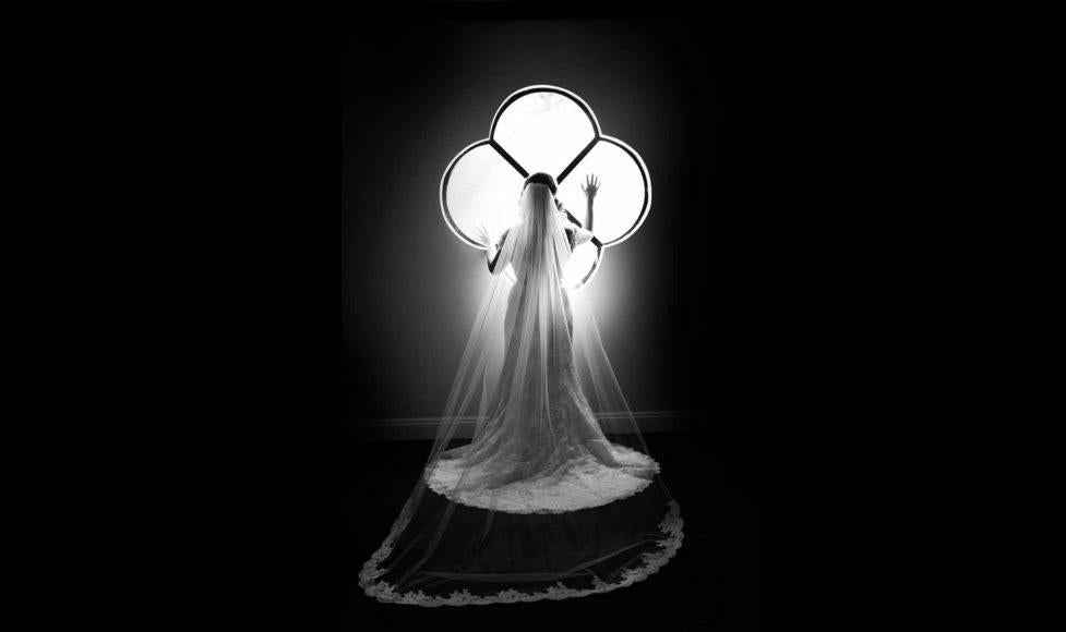 black and white photo of bride leaning against window with hands on window