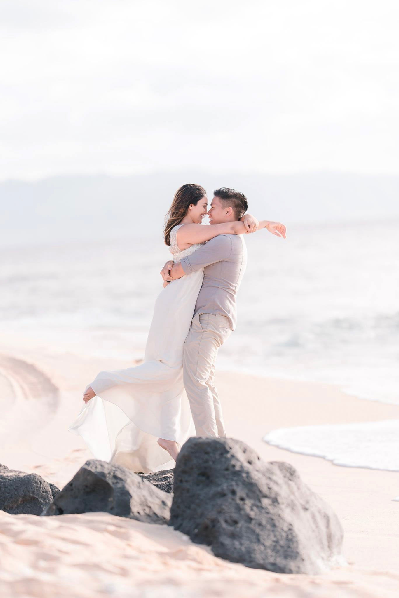 A bride and groom hugging each other at a beach