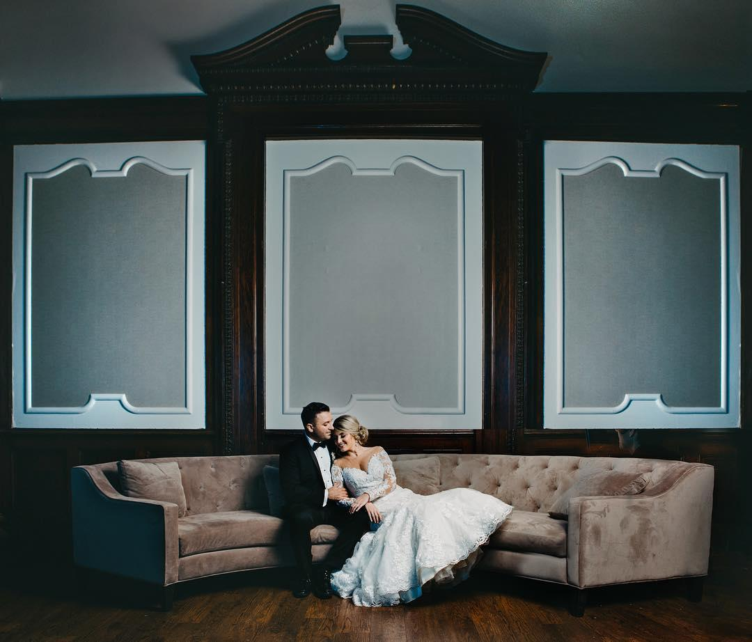 couple cuddling on a couch in wedding clothes