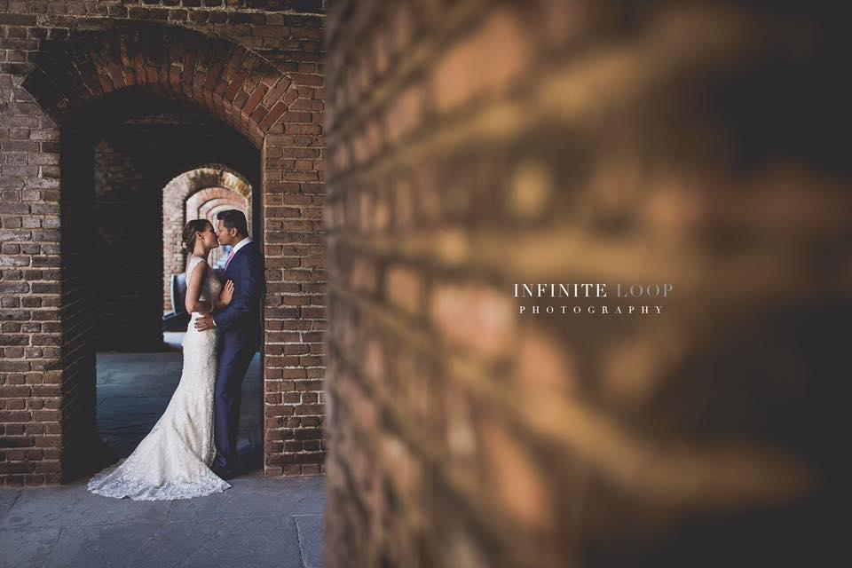 A bride and groom embracing against exposed brick.