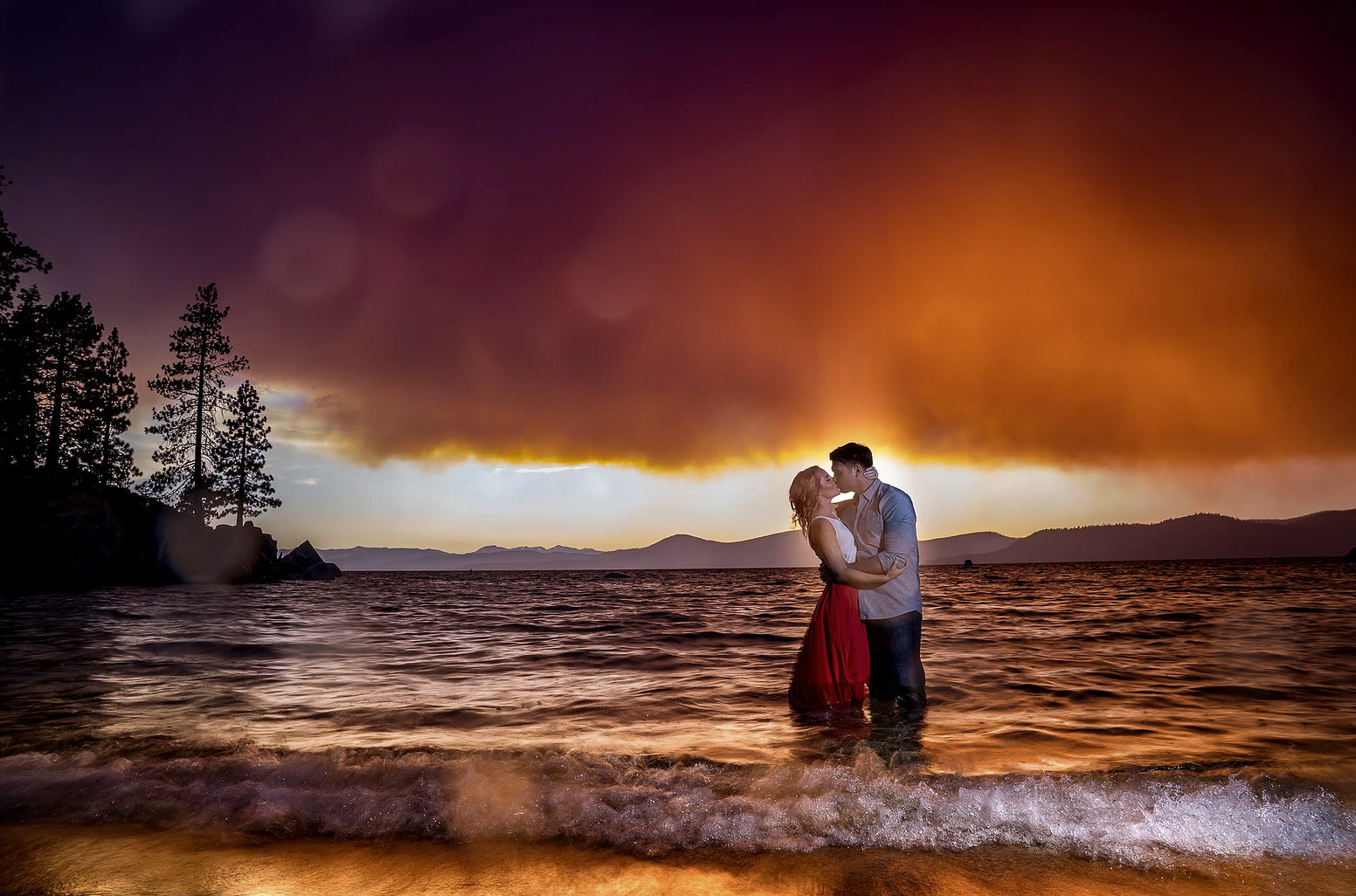 A couple kissing each other while standing on the beach with their feet immersed in seawater during sunset