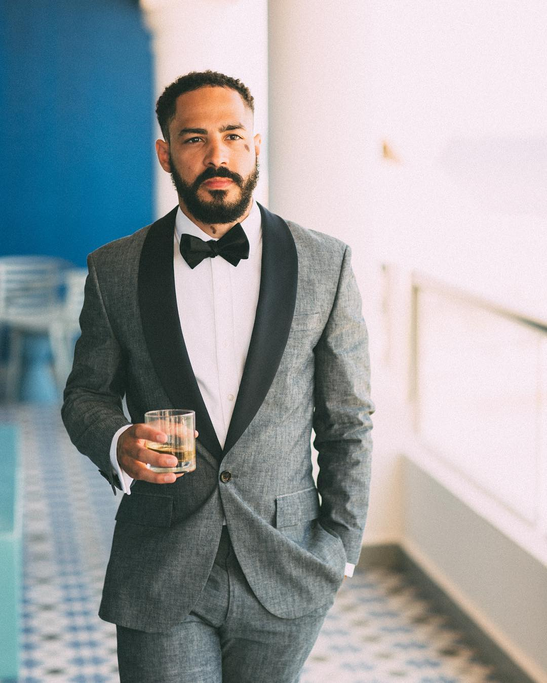 Portrait of a groom dressed in a tuxedo walking towards the camera while holding a glass