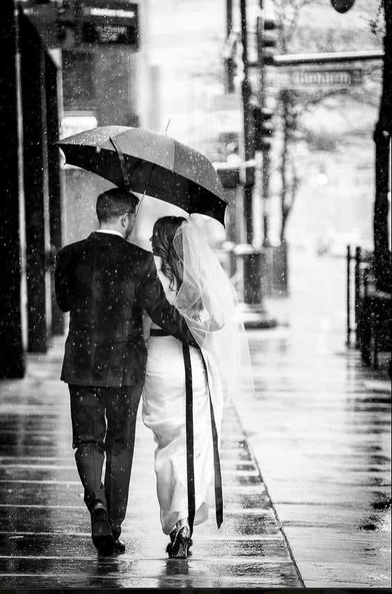 black and white image of a couple wearing wedding dress and tux walking in rain under umbrella