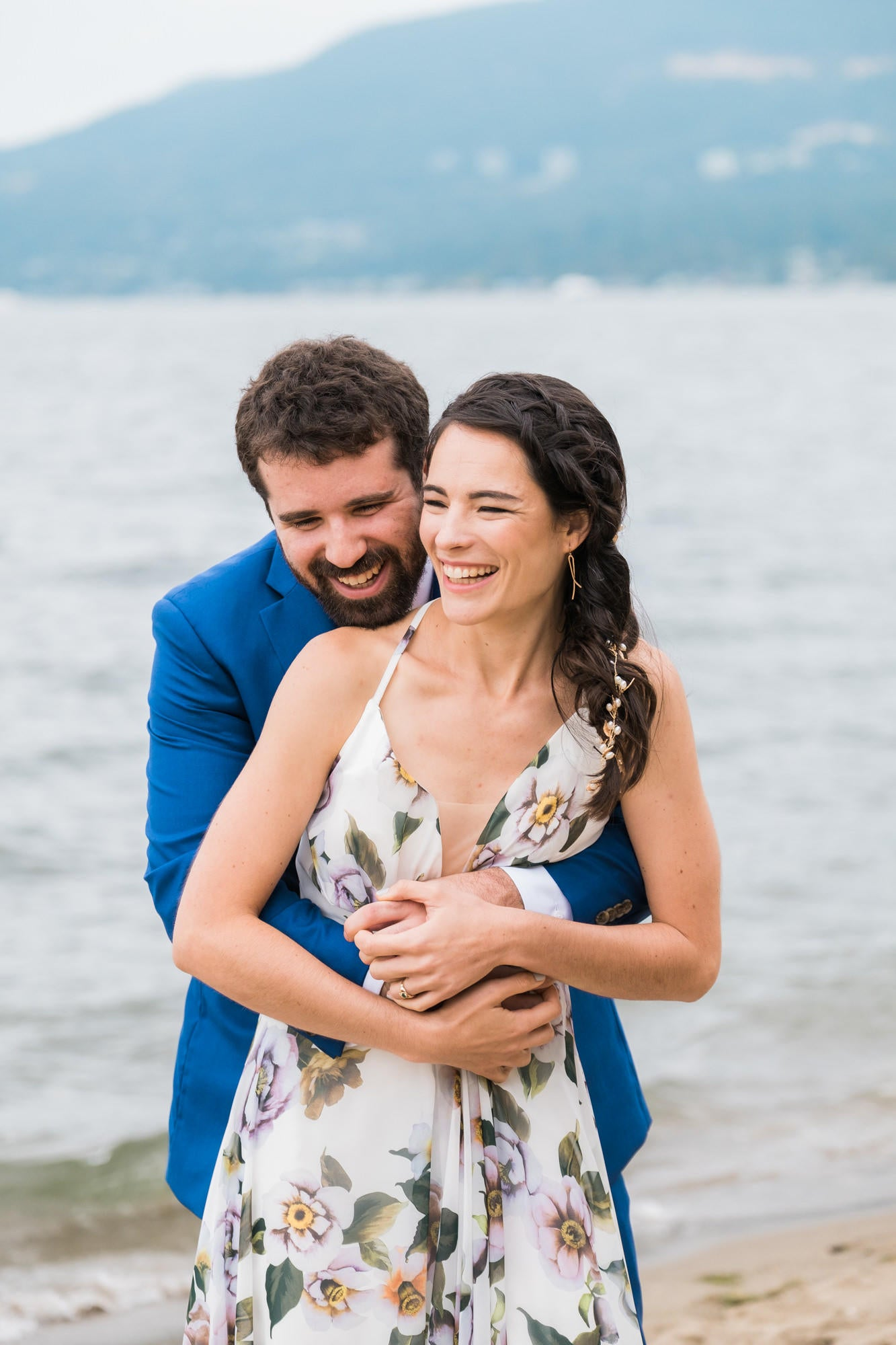 couple leaning into each other and laughing on the edge of the water with a hill behind them