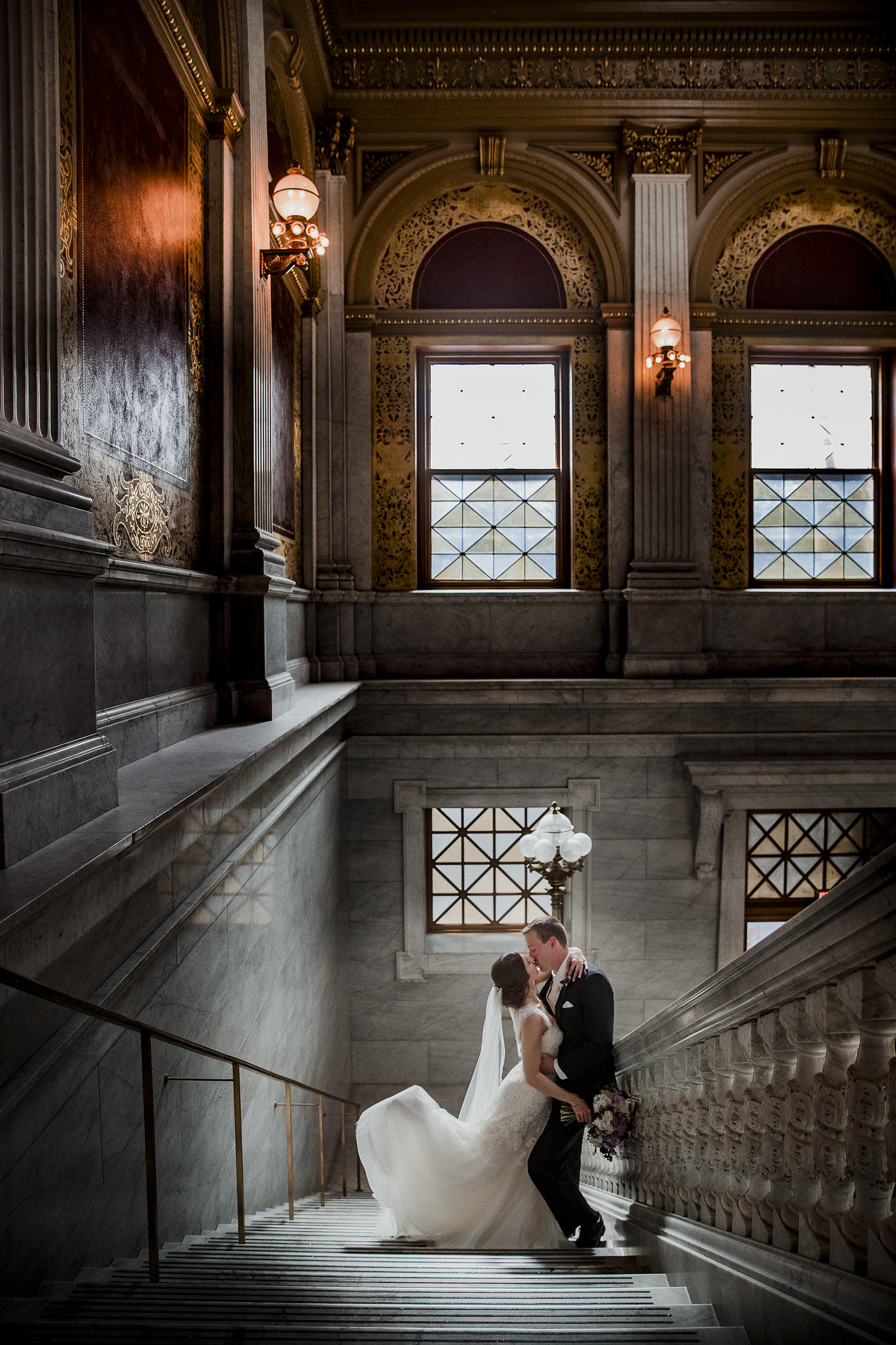 couple embracing and kissing while standing on a stone staircase wearing wedding clothes