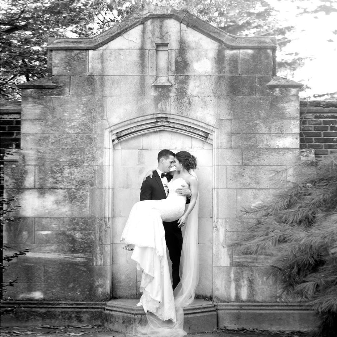 Black and white photo of a groom holding the bride in his arms in front of a wall