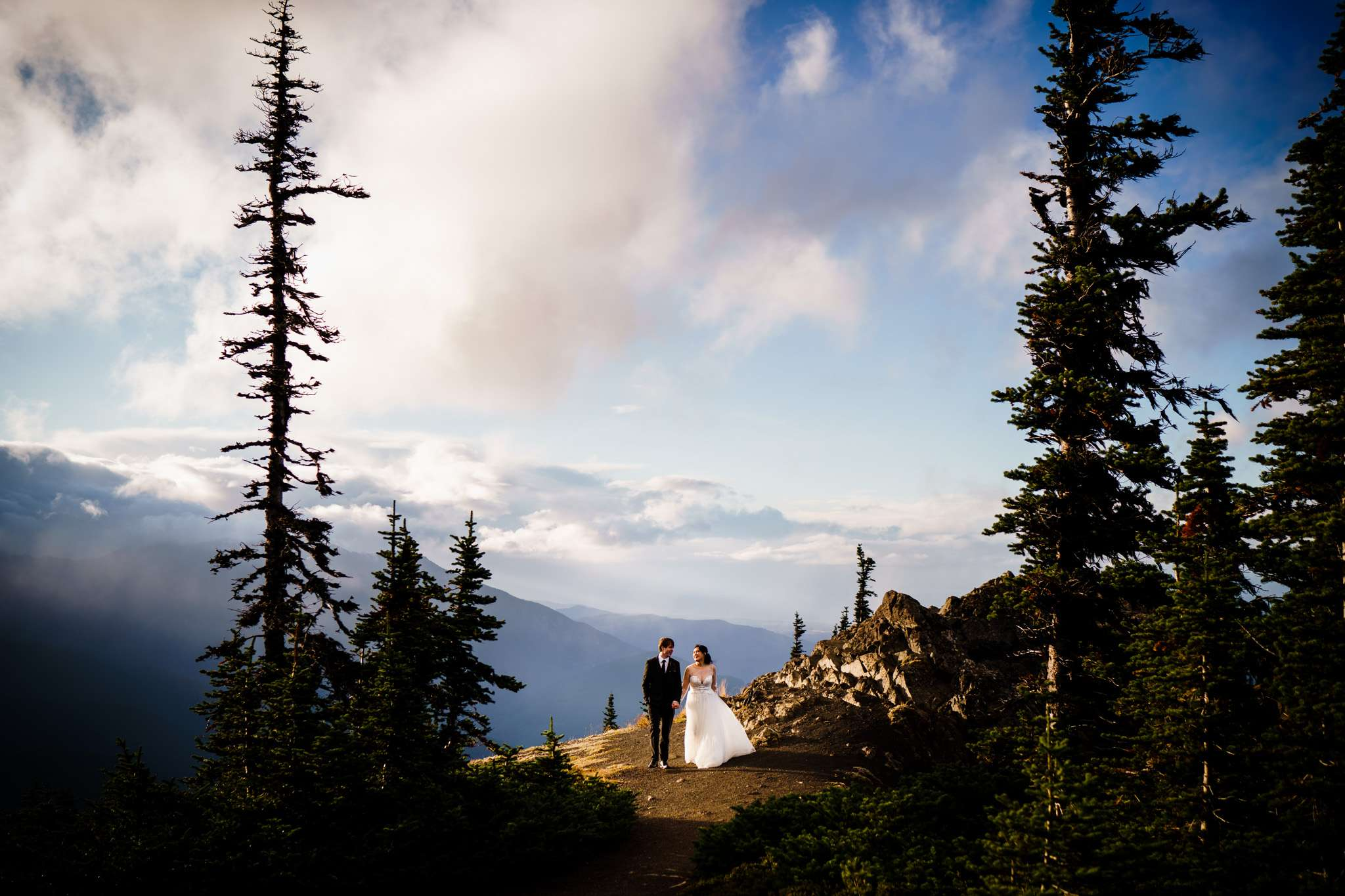 A bride and groom walking hand in hand on top of a cliff