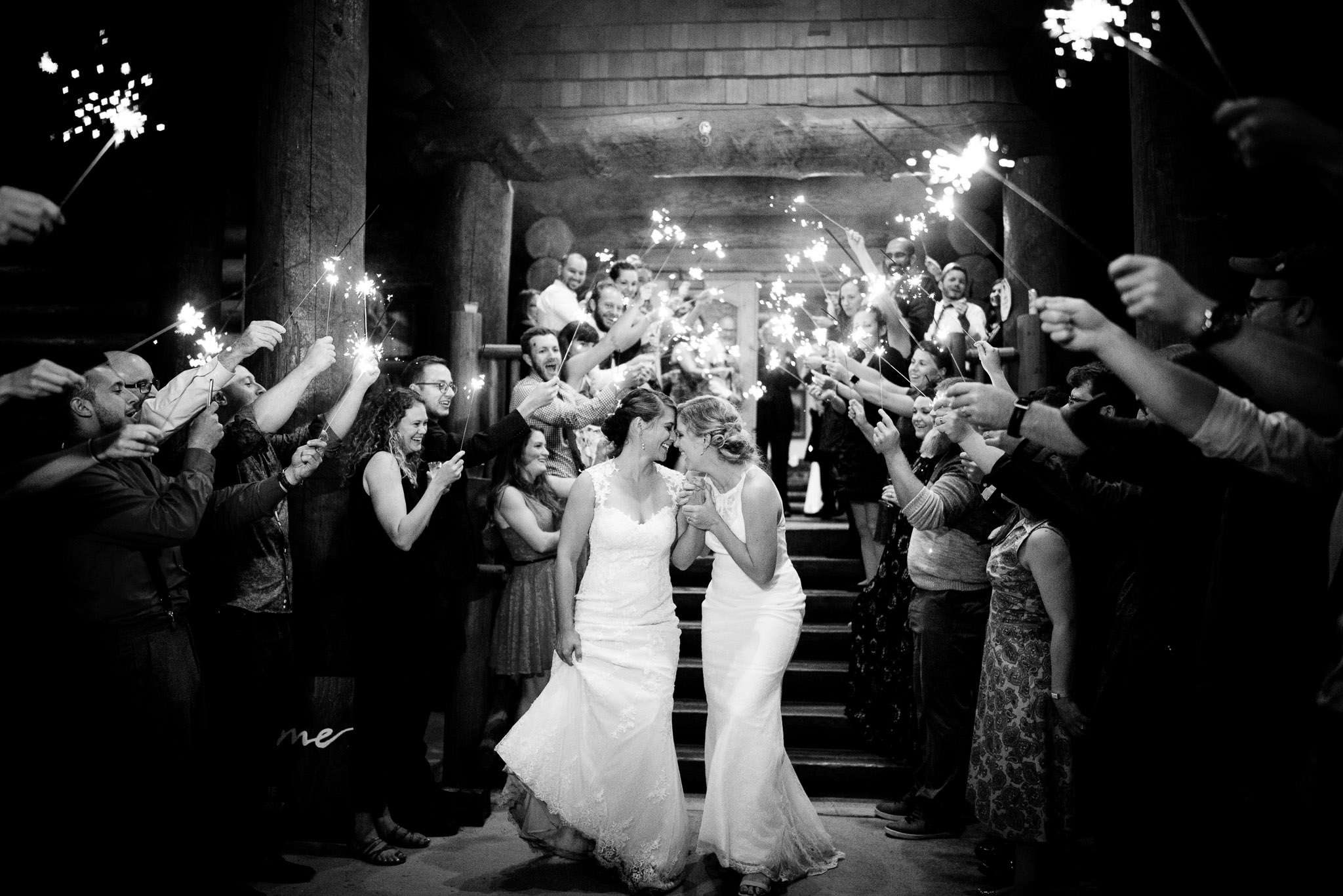 Black and white image of a couple of two brides walking through the exit as the guest lit sparklers