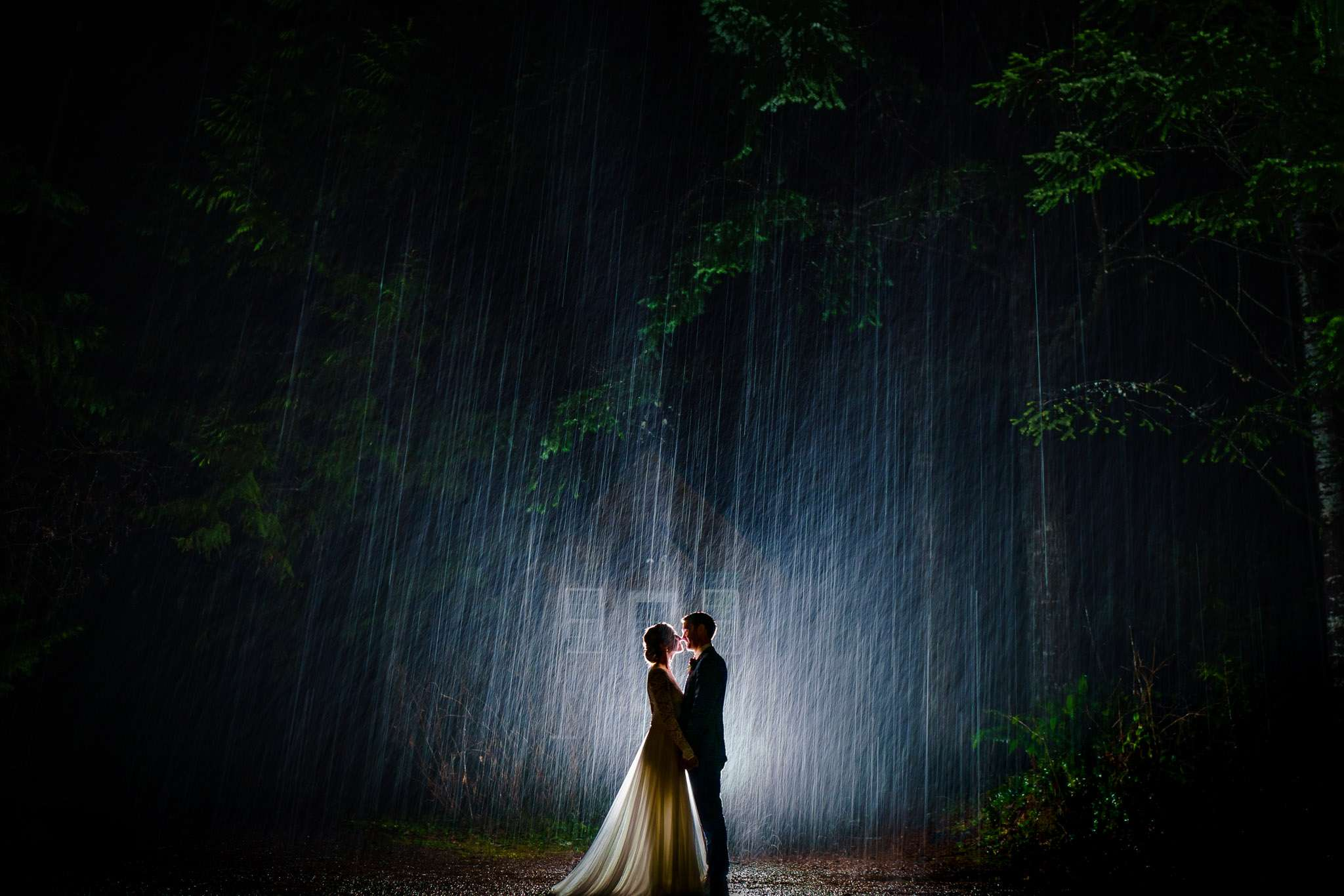 Silhouette of a bride and groom kissing in the rain