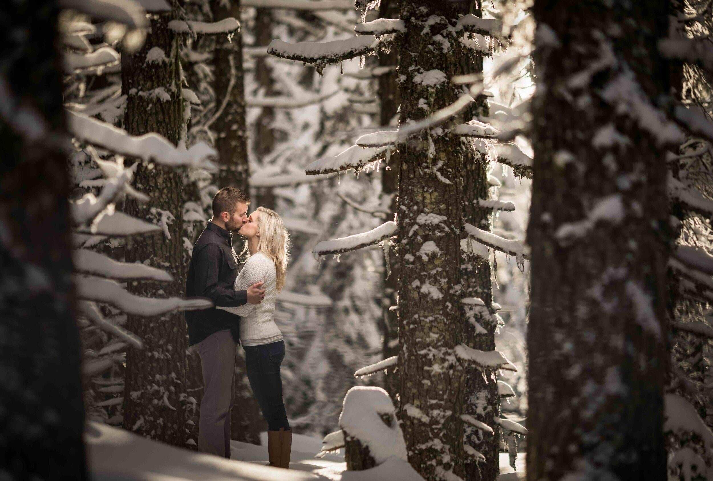 couple kissing in snow covered forest