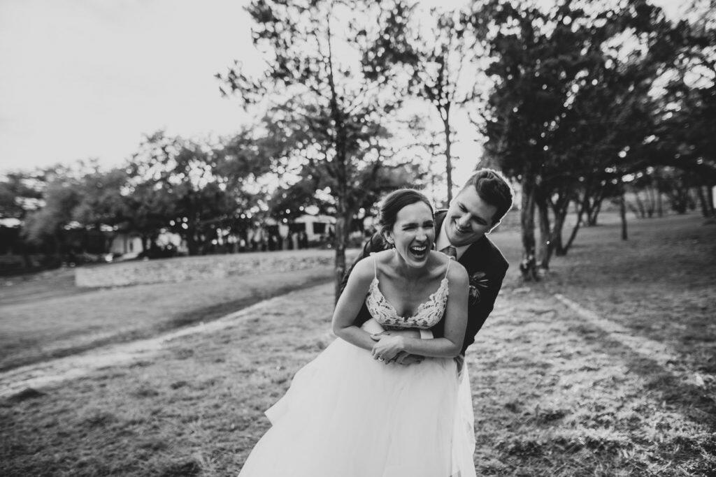 Black and white photo of a bride and groom laughing as they hug each other
