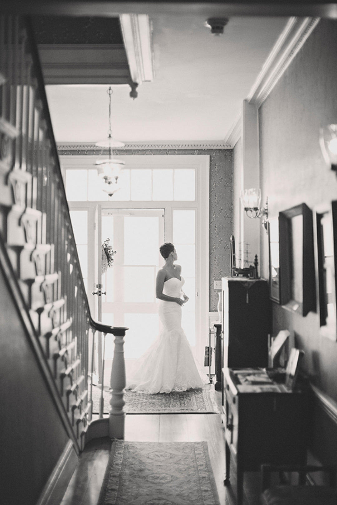 Black and white image of a bride in a hallway