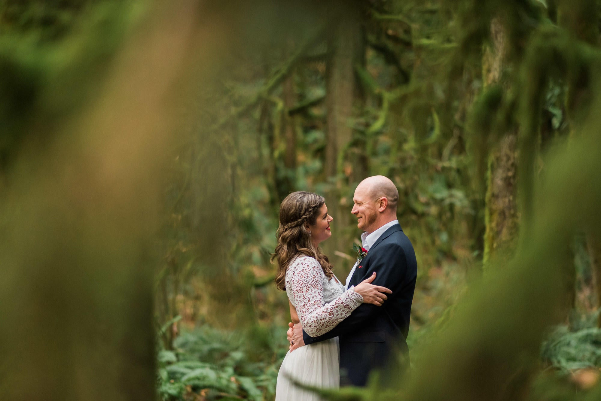 bride and groom looking at each other in a dense green forest