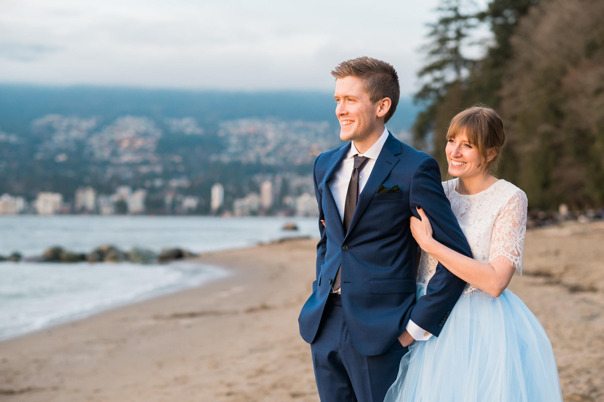bride and groom walking arm in arm on a beach facing the sun