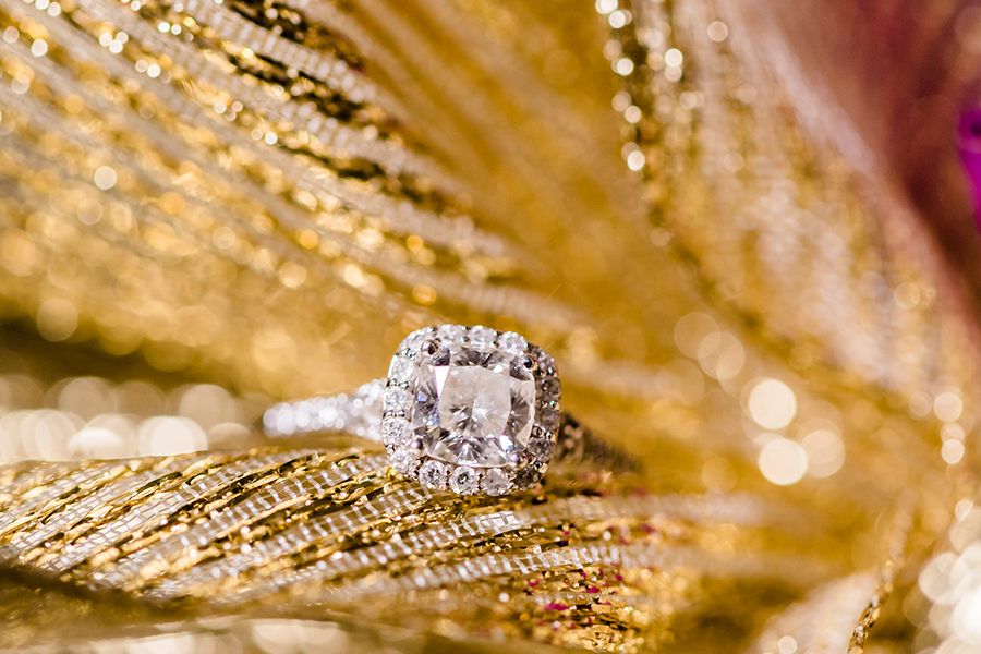 A silver ring sitting on additional gold and silver jewelry.