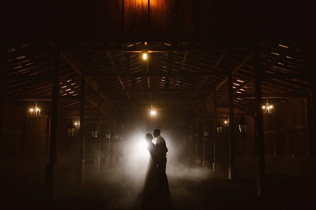 Silhouette of a couple holding each other in a dimly lit and smoky corridor