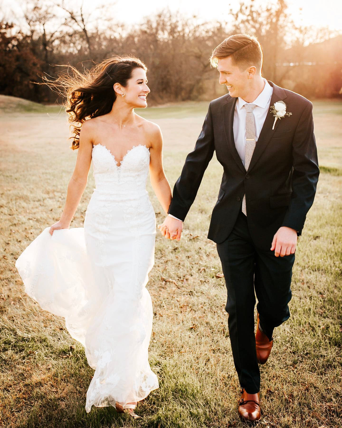 A bride and groom walking while holding hands
