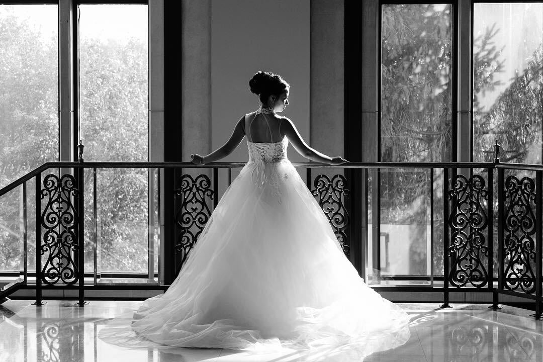 black and white photo of bride looking out over tall windows