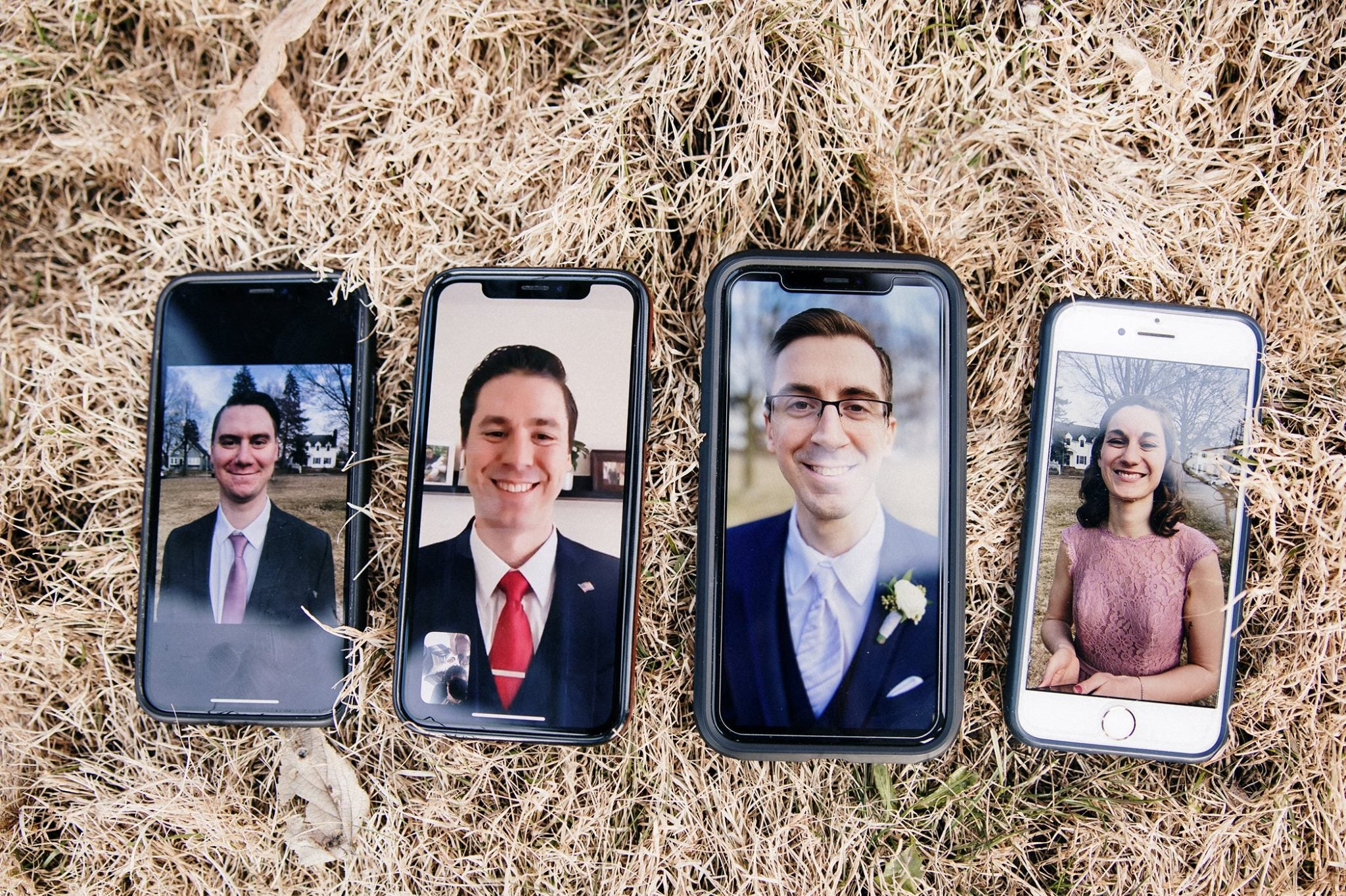 Four smart phones placed on top of a hay covered platform showcasing people video calling