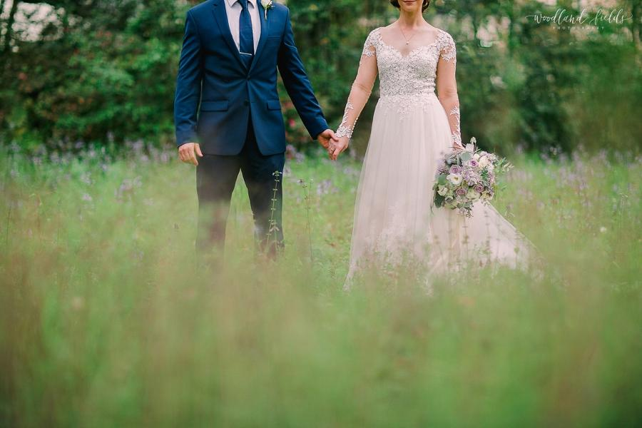 Bride and groom holding hands in an image taken by Catherine Taylor of Woodland Fields Photography