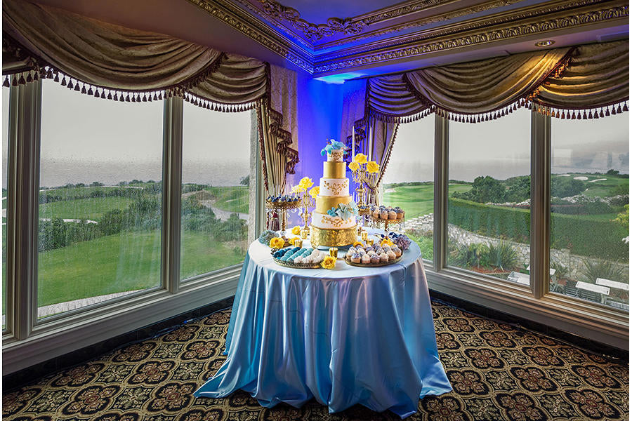 A wedding cake photo with the cake on the table, along with cupcakes, uplighting behind the table, and open windows in the background.