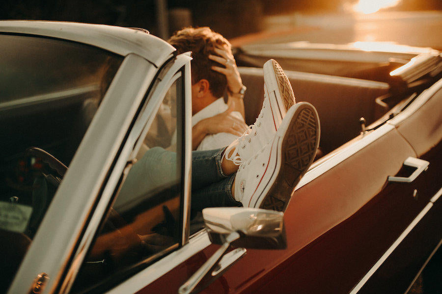 A sunset engagement session photo of the couple sitting in a car with only the bride's sneakers, hand with her ring, and the back of the groom's head are showing.
