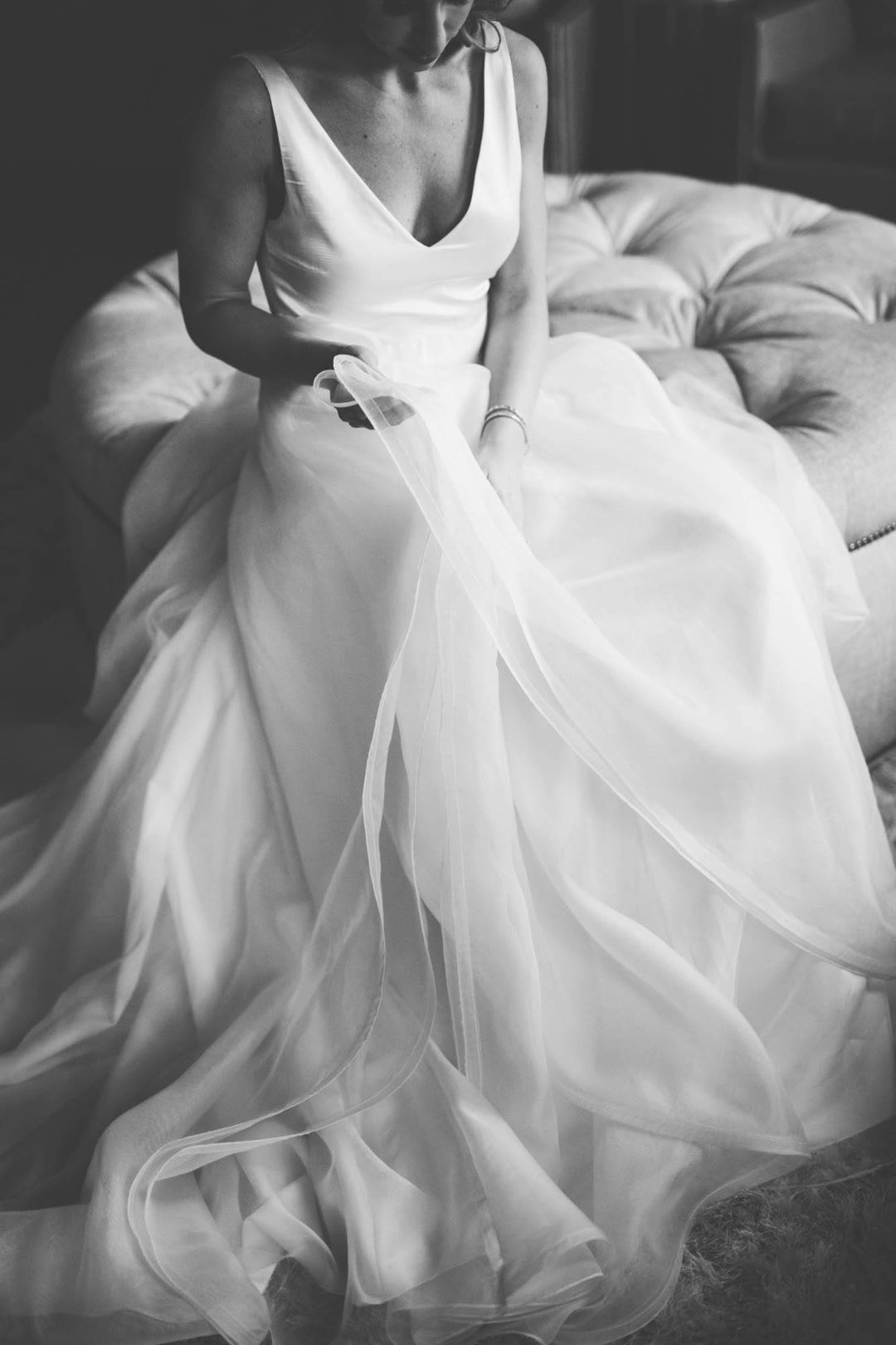 Black and white photo of a bride holding the skirt of her bridal dress