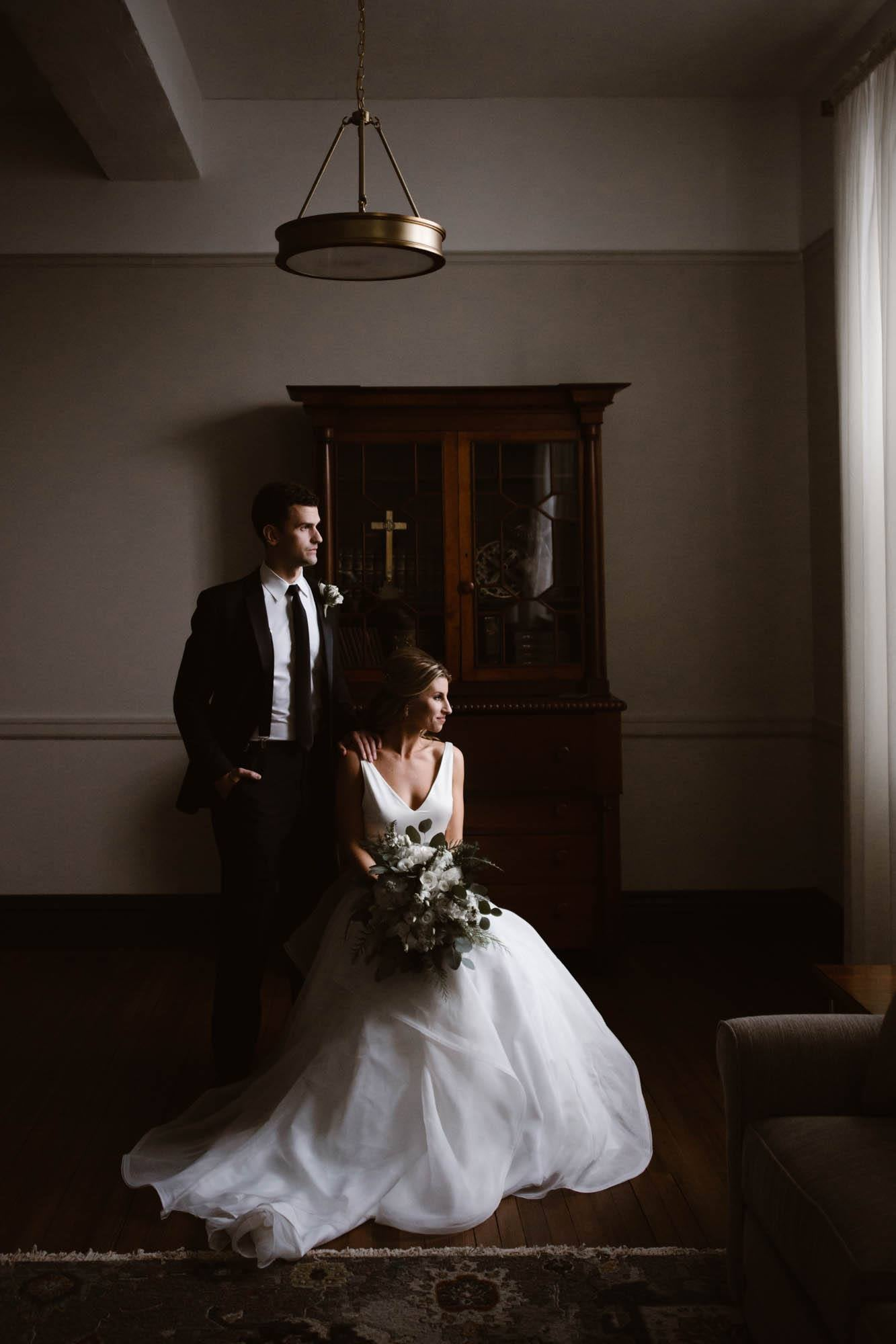 A bride and groom posing while sitting on a chair that is placed in front of a window