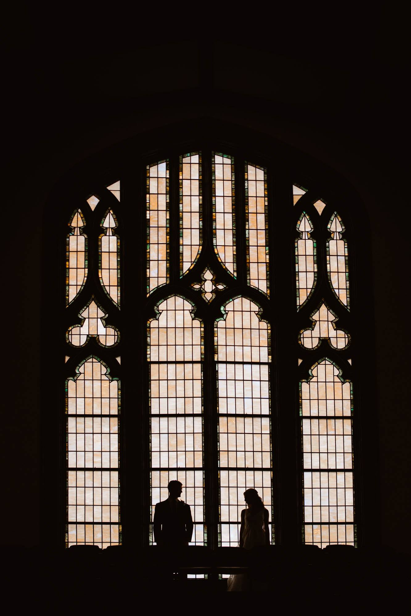 Silhouette of a bride and groom standing in front of a window in a church
