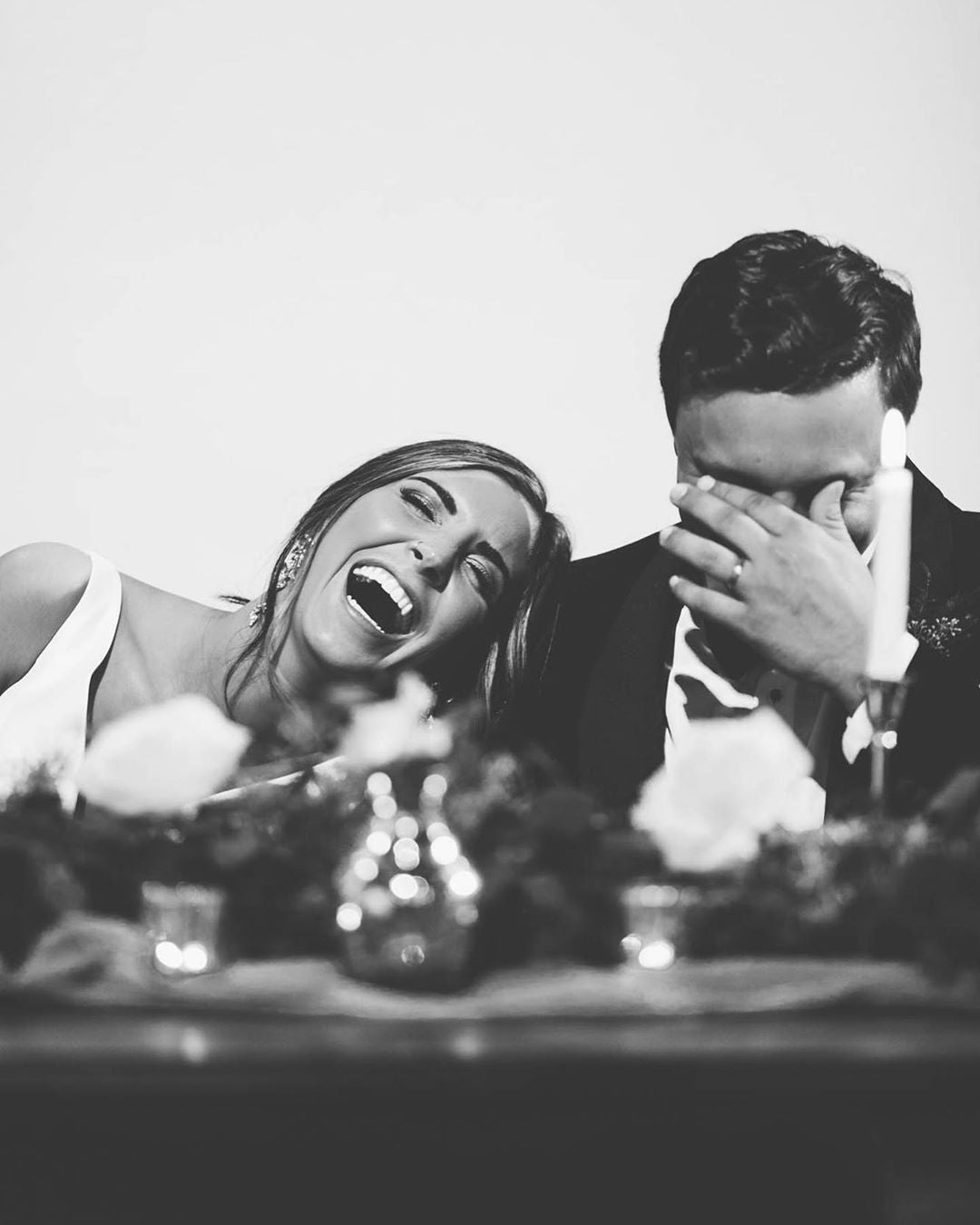 Black and white portrait of a couple laughing over the dinner table with the bride leaning over the groom's shoulder
