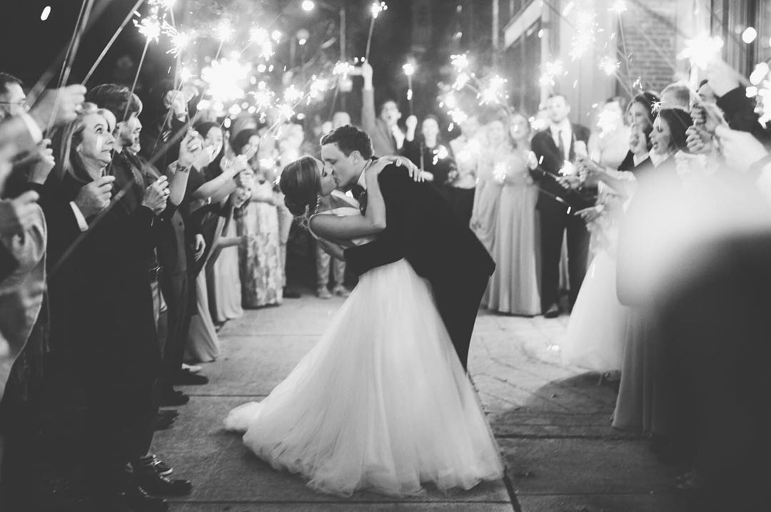 A bride and groom kissing during the exit at the wedding reception as the guest surround them with sparklers