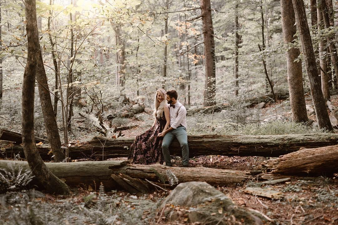 couple sitting on log in a forest
