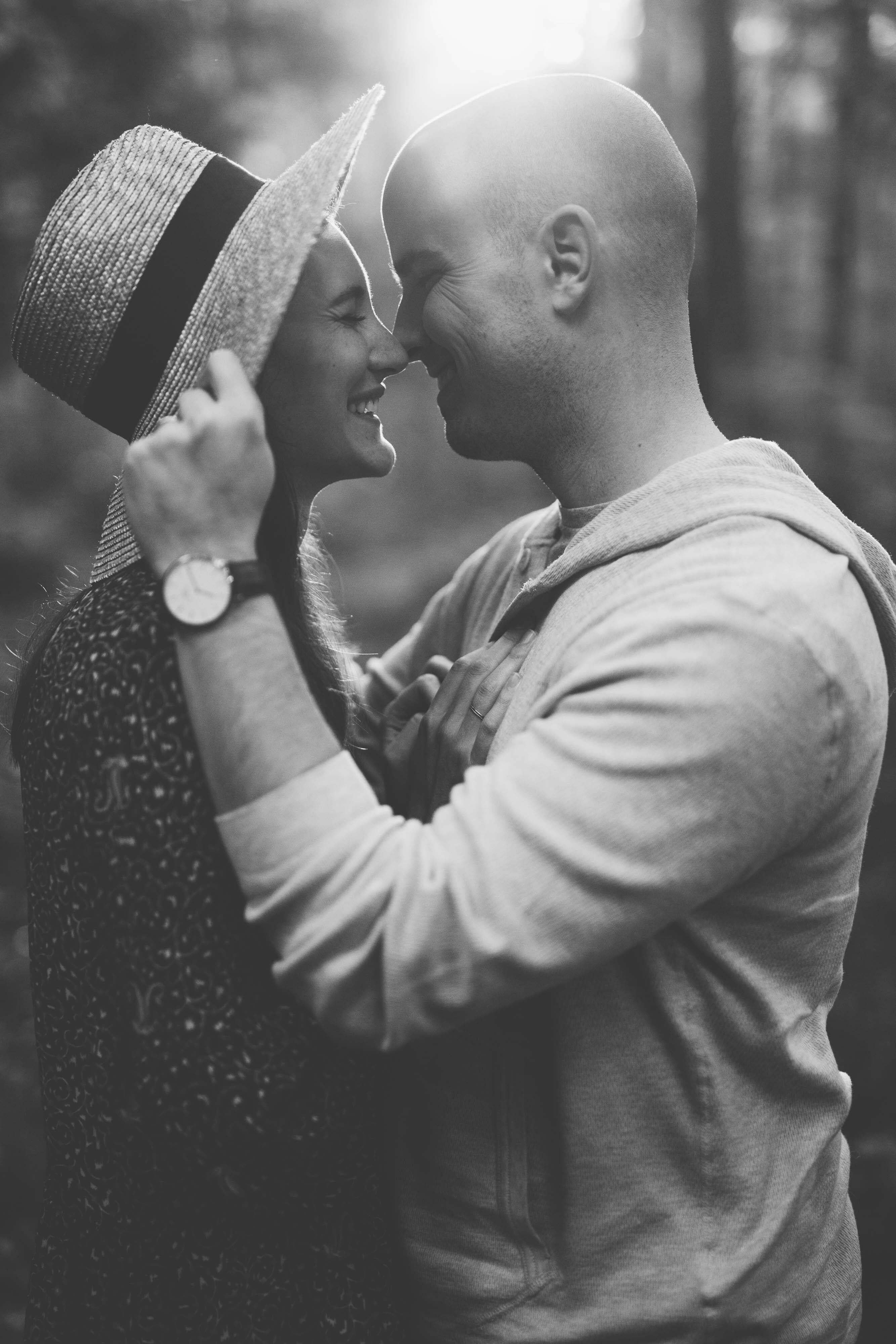 Black and white image of a couple smiling & facing each other with the guy reaching for the girl's hat.