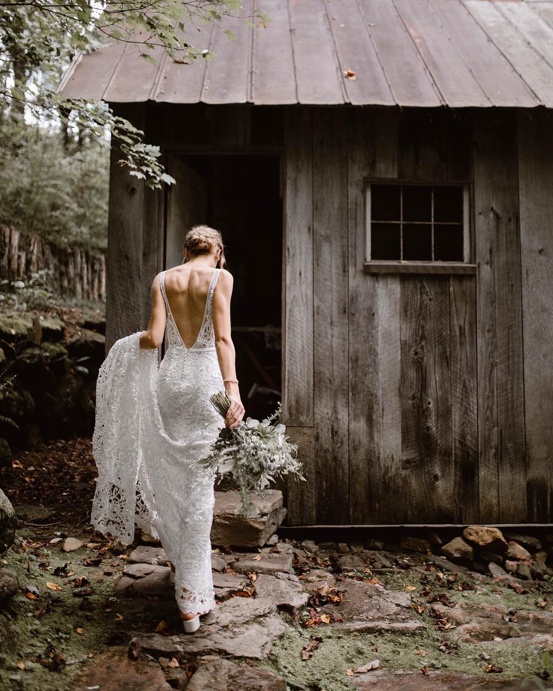 A bride holding the train of her dress from one hand and the bouquet from the other walks into a hut