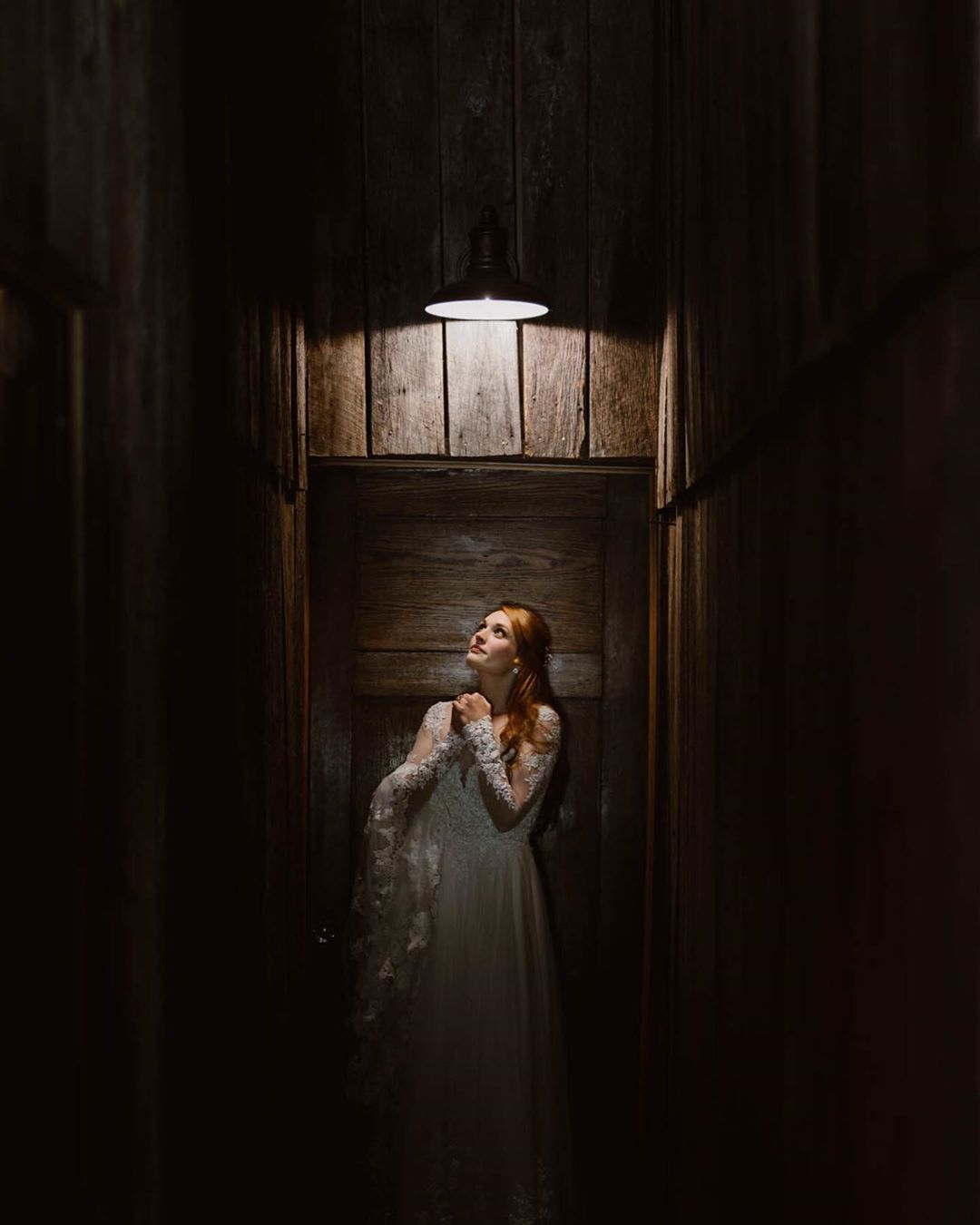 Portrait of a bride standing right the light source in an enclosed space